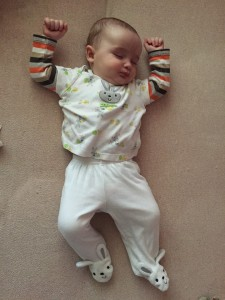 Baby infant dressed in first easter shirt and pants with bunny feet