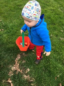 Toddler carrying easter basket bucket filled with eggs on grass