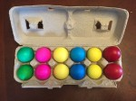 Easter eggs filled with confetti in egg carton arranged by color
