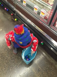 Young child collecting easter eggs in basket at grocery store