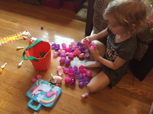 Child with pink and purple plastic Easter eggs opened in pile on floor