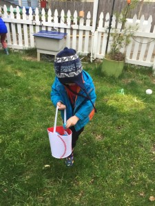 Young child hunting Easter eggs in grass with white picket fence