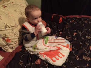 Infant drinking from bottle while wearing a sleep sack