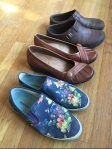 Slip on shoes lined up on floor from SeaVees Hush Puppies and Merrell