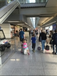 Kid riding on Jetkids BedBox being pulled by sibling through busy airport