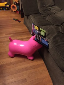 Pink dog inflatable ride on toy propping up book next to sofa
