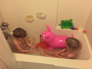 Children in bath tub with Pink Dog inflatable ride on toy by Wahoo