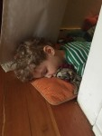 Four year old passed out on pillow on floor