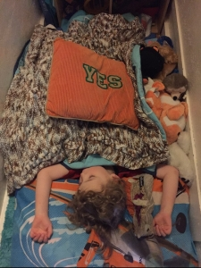 Four year old passed out sleeping on floor with pillows and blanket