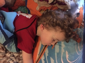 Four year old napping on closet floor with pillows and blankets