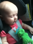 Infant sleeping in car seat with green frog wubbanub pacifier stuffed animal attached