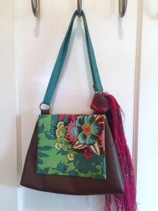 Pink printed scarf tied to handle of printed purse hanging on door