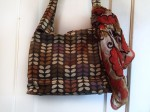 Orla Kiely diaper changing bag with multicolor infinity scarf tied to handle hanging on door