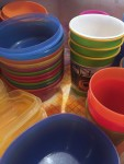 Stacks of brightly colored kids dishes cups and bowls