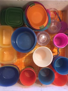 Kitchen drawer full of kid dishes cups bowls straws in bright colors and clear containers as seen from above