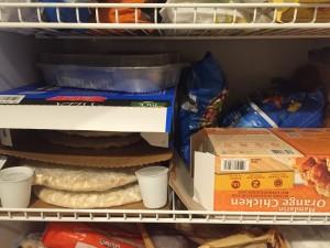 Shelf of family freezer food frozen pizza orange chicken