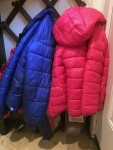 Pink and blue children's puffy winter coats hanging side by side