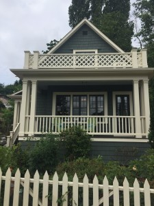 White picket fence and house with white railing