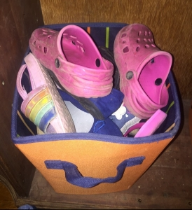 Kids Crocs sandals tennis shoes sneakers shoes piled into orange storage bin