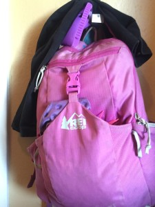 Black leggings hanging on top of child's REI backpack for school