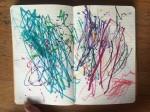 Child's scribbles inside lined moleskin journal