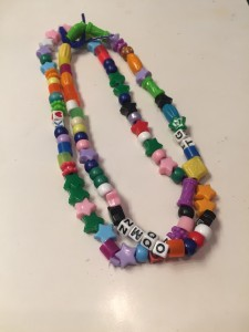 Bead necklace made by child in colored plastic beads on ribbon
