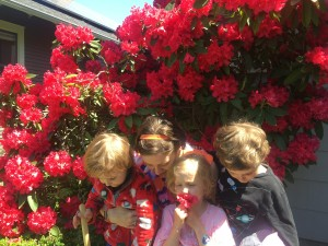 Mom with three kids looking down in front of red rhododendron bush for Mother's Day photos