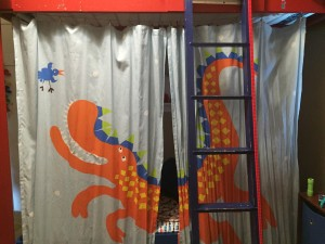 Curtain screen for lower bunk bed hanging behind ladder