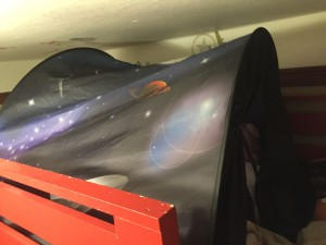 dream tent space theme installed in upper bunk near ceiling