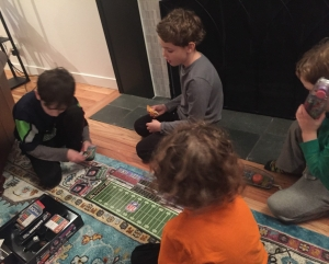 Kids playing football board game on floor