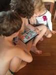 Three kids gathered around ipad playing cooperative electronic game Toca Farm app