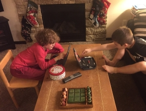 Two kids playing battleship in front of fireplace