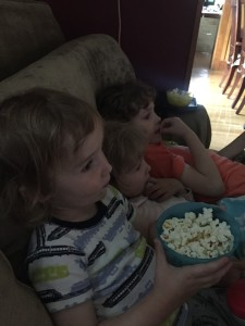 Three kids sitting on sofa in the dark with bowl of popcorn watching movie