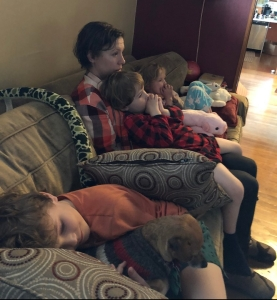Family of mom and three kids sitting on sofa watching a movie