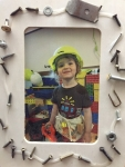 Child wearing hardhat in frame decorated with nails and screws
