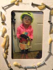 Child wearing hard hat and holding drill in photo frame decorated with nails and screws