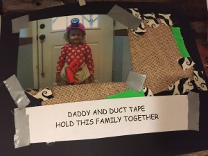 Child wearing hard hat in paper photo frame decorated with duct tape