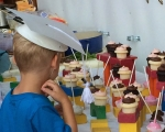 Child wearing homemade graduation hat craft for young kids blocks as mini cupcake stands