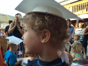 Child wearing graduation hat craft from bowl and cardboard at kids' party