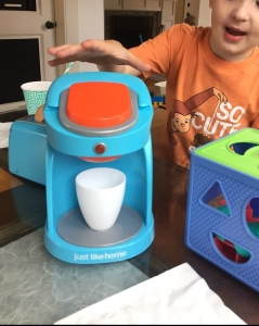 Child playing with Just Like Home kids coffee maker toy appliance light blue with orange