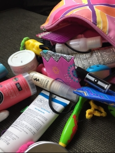 Bag with travel bathroom supplies pouring out hairspray toothbrush packing list