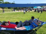 Mac Sports Fold Up Portable Hammock with Shade in blue and gray set up at park festival sunshine