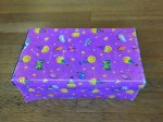 Shoebox covered in purple wrapping paper filled with small toys as rewards for kids