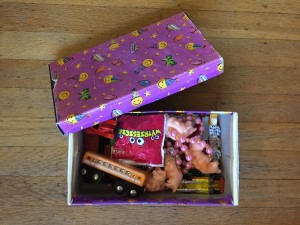 Shoe box with open lid covered in purple wrapping paper and filled with small toys as rewards for kids