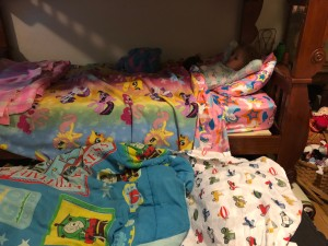 Bunk bed with trundle and pink kid unicorn sheets and white construction vehicle sheets