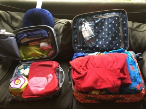 Child's suitcase and roller board packed for three day travel with three kids