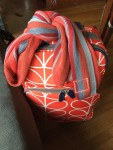 Orla Kiely orange flower print roller board suitcase with knitted striped scarf tied to handle