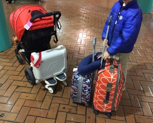 Suitcases and stroller parked for travel with young kids
