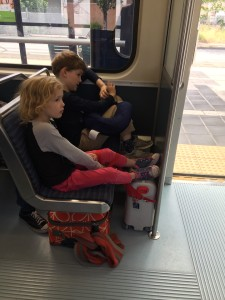 Kids traveling on city train with luggage under their feet