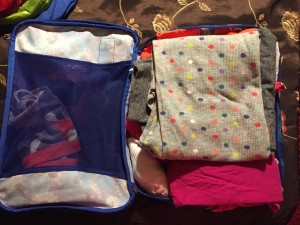 Clothes packed into open Eagle Creek pack it cube large with blue flower print